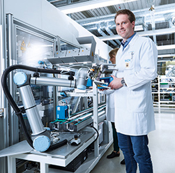 man standing next to robotic arm used in electronics industry
