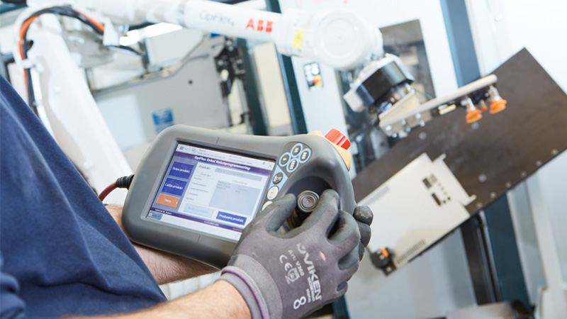 Technician controls OpiFlex robot arm to safely life lift large box